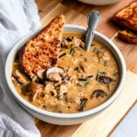 a bowl of mushroom wild rice soup with toast