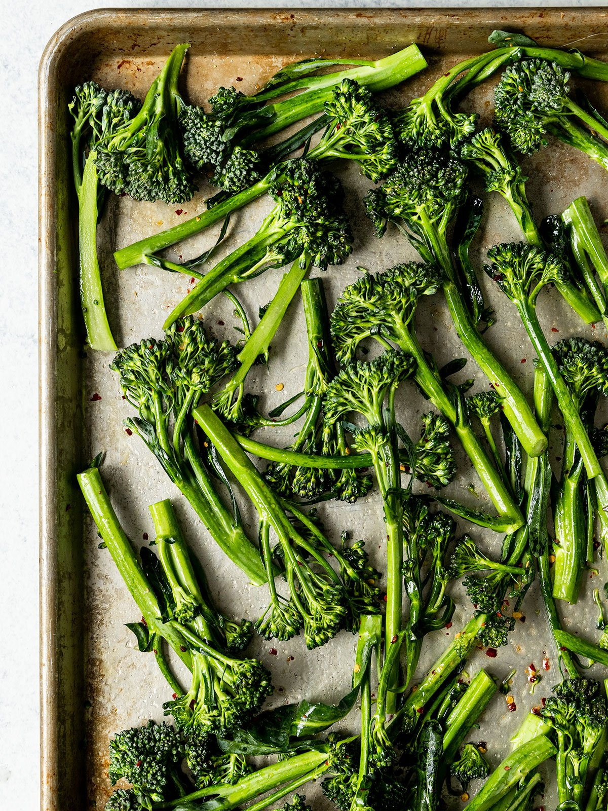 tray topped with uncooked and seasoned broccolini