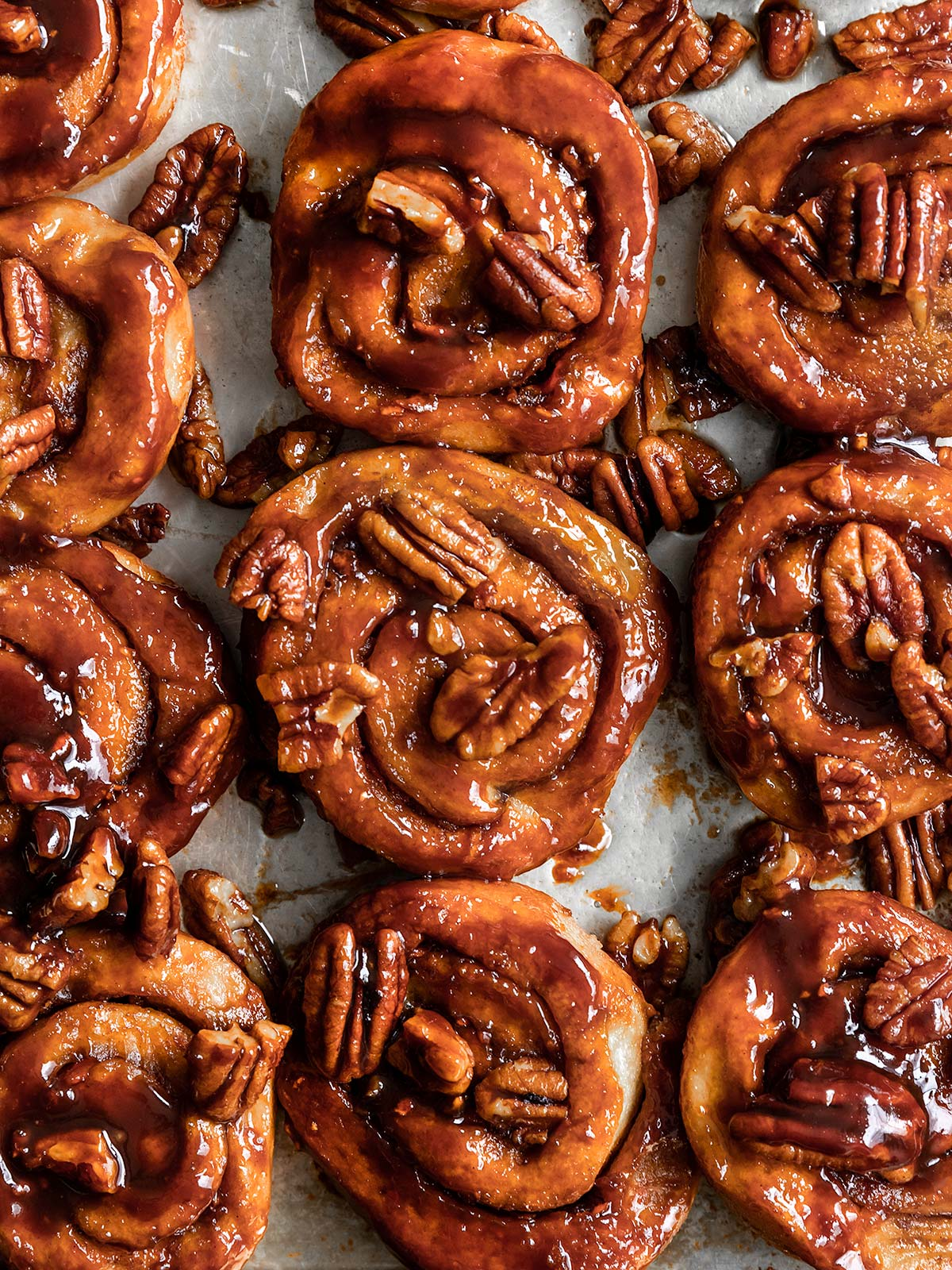vegan sticky buns on a baking tray with pecans