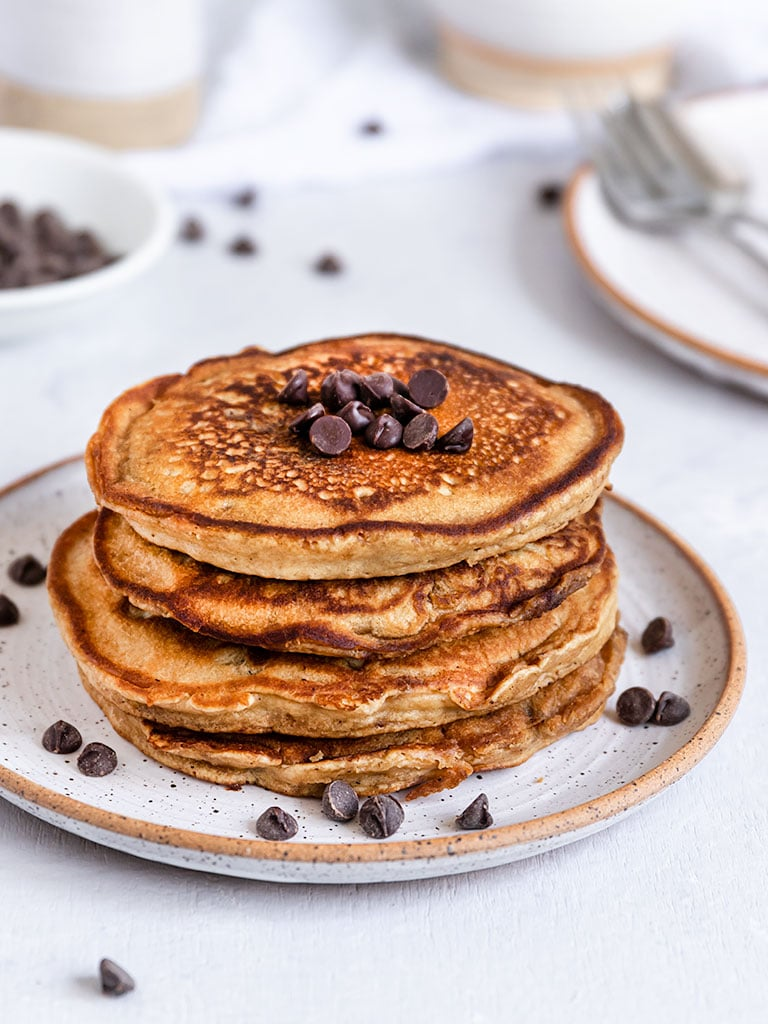 a stack of four chocolate chip pancakes with chocolate chips on top