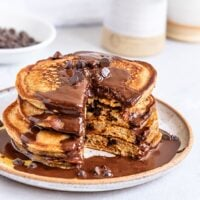 chocolate chip pancakes covered in chocolate sauce with a bite taken out