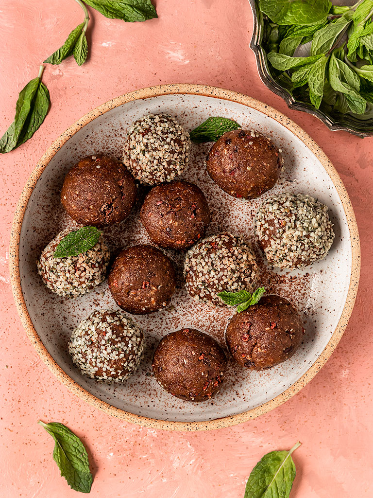 mint bliss balls in a bowl with hemo seeds and fresh mint
