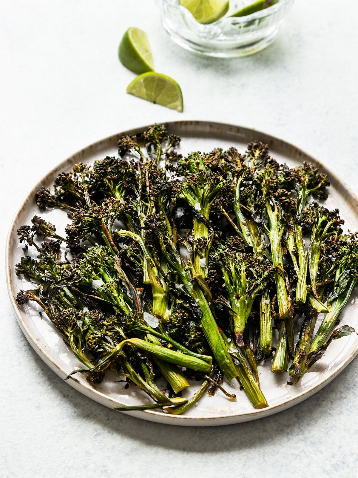 a plate full of broccolini with lime wedges