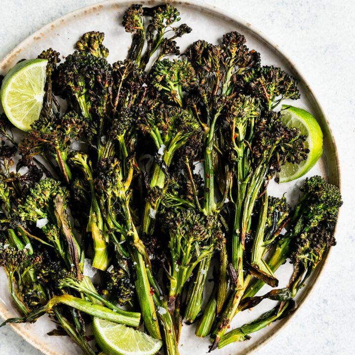 a plate full of broccolini with lime wedge and flaky salt