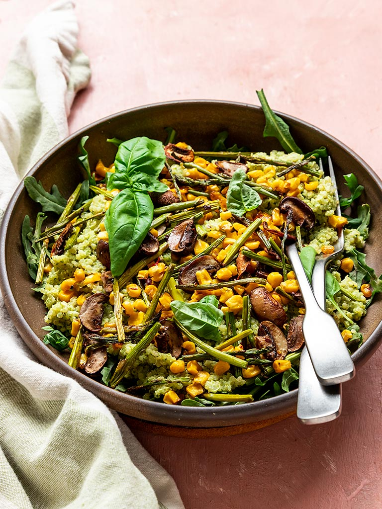 a bowl filled with quinoa pesto, corn, asparagus, mushroom, and fresh basil