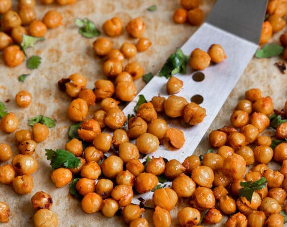 baked chickpeas with cilantro being scooped off a baking sheet