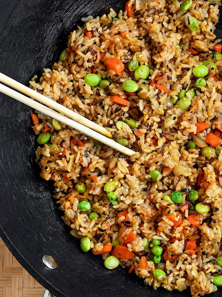 a wok filled with vegan fried rice with edamame, peas, carrots, onions, and furikake seasoning