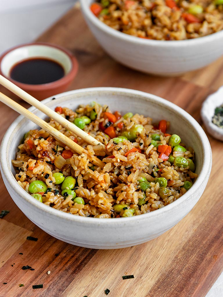 chopsticks taking out a bite of vegan fried rice from a bowl