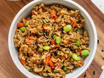 a bowl of fried rice with vegetables like edamame, carrot, onion, and peas