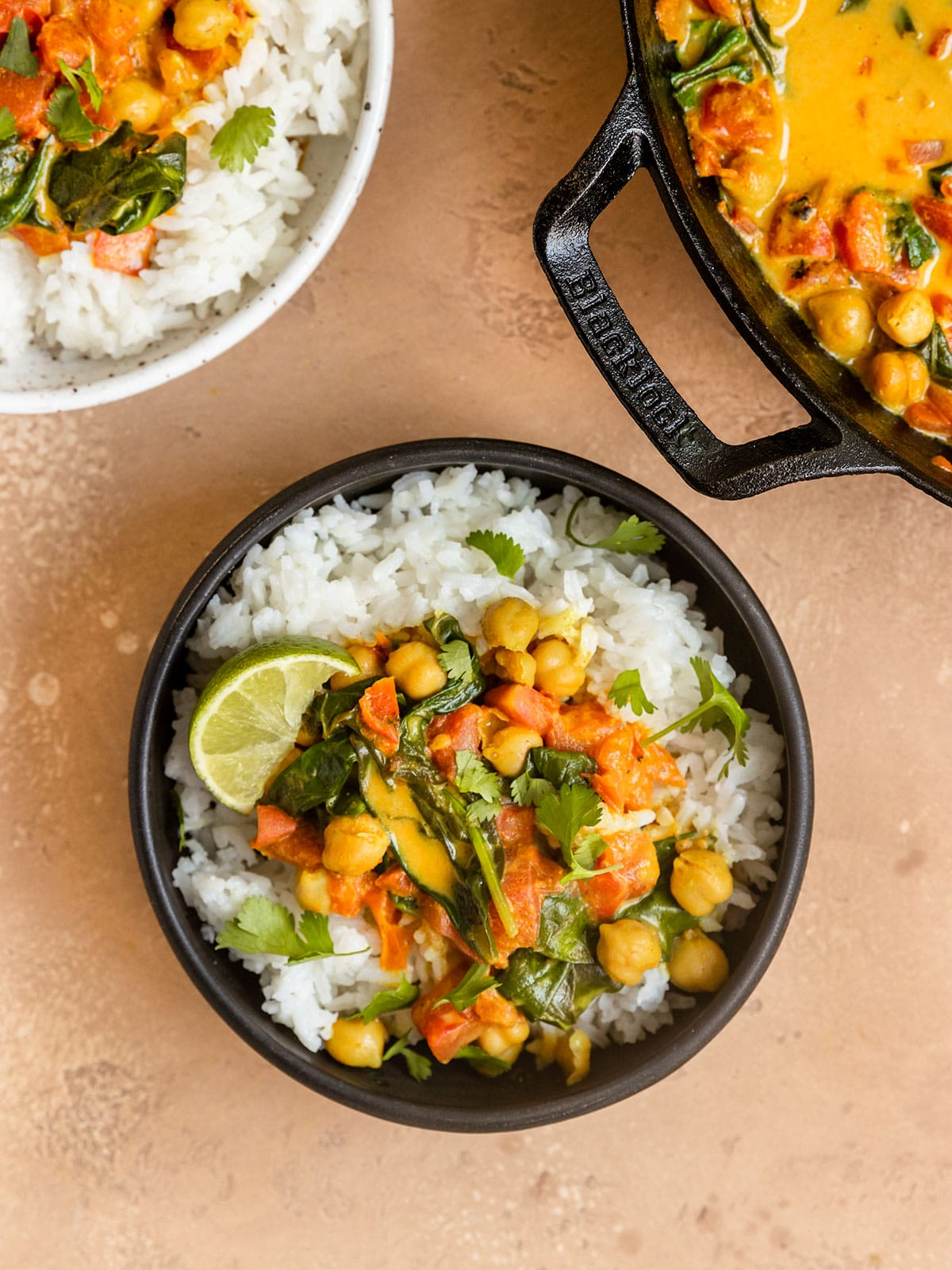 three bowls filled with chickpea tomato spinach curry with cilantro and lime