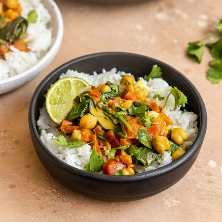 bowl with chickpea tomato spinach curry and cilantro and lime on top
