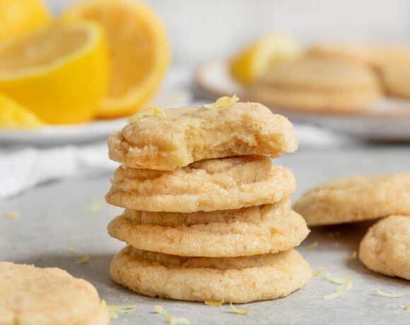 stack of lemon sugar cookies with lemon zest and fresh lemons