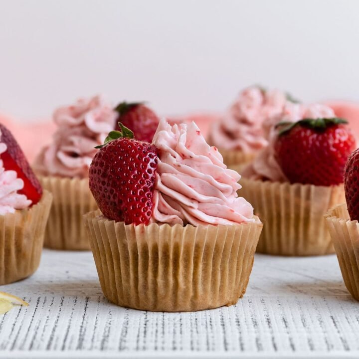 cupcakes with strawberry frosting and fresh strawberries on top