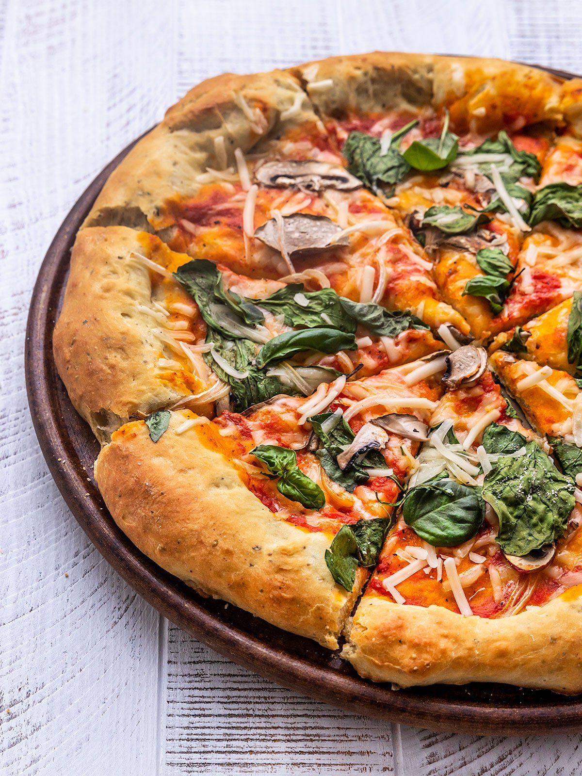pizza sliced with spinach, basil, cheese, tomato sauce, mushroom, and onion toppings
