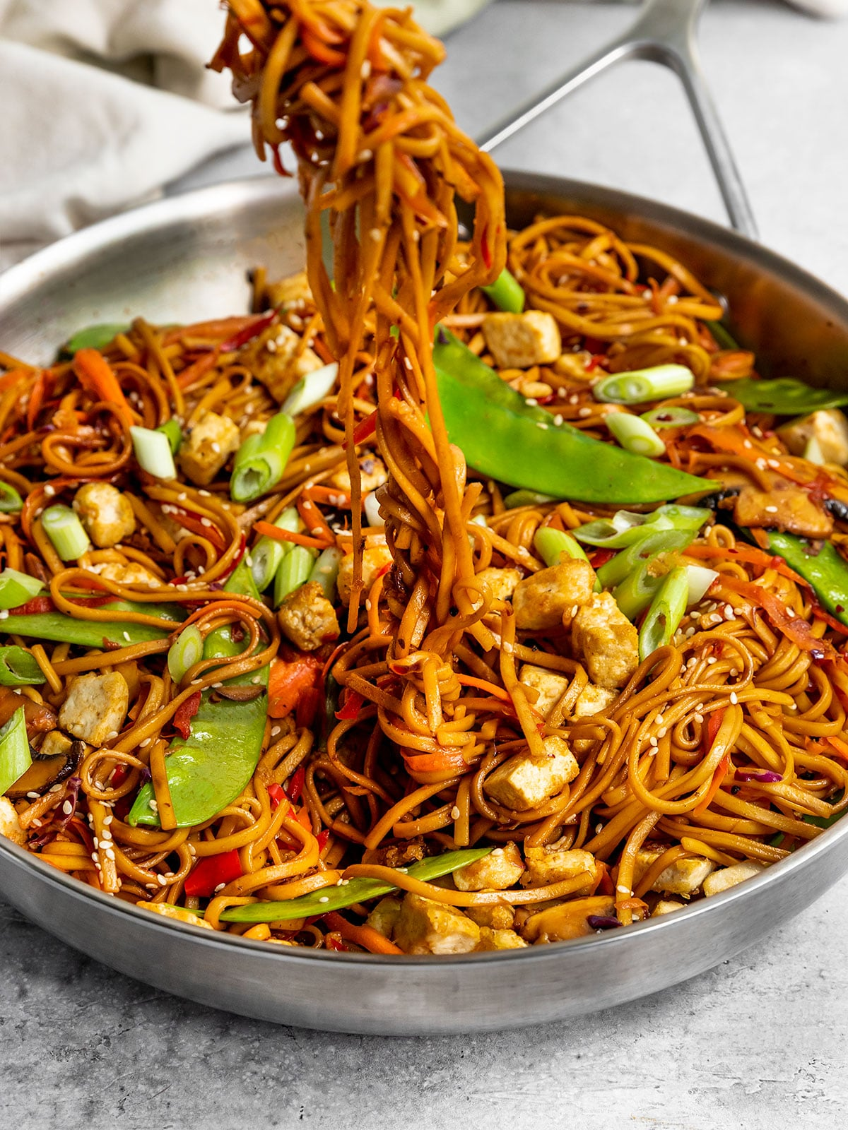lo mein noodles with vegetables being pulled out of a pan