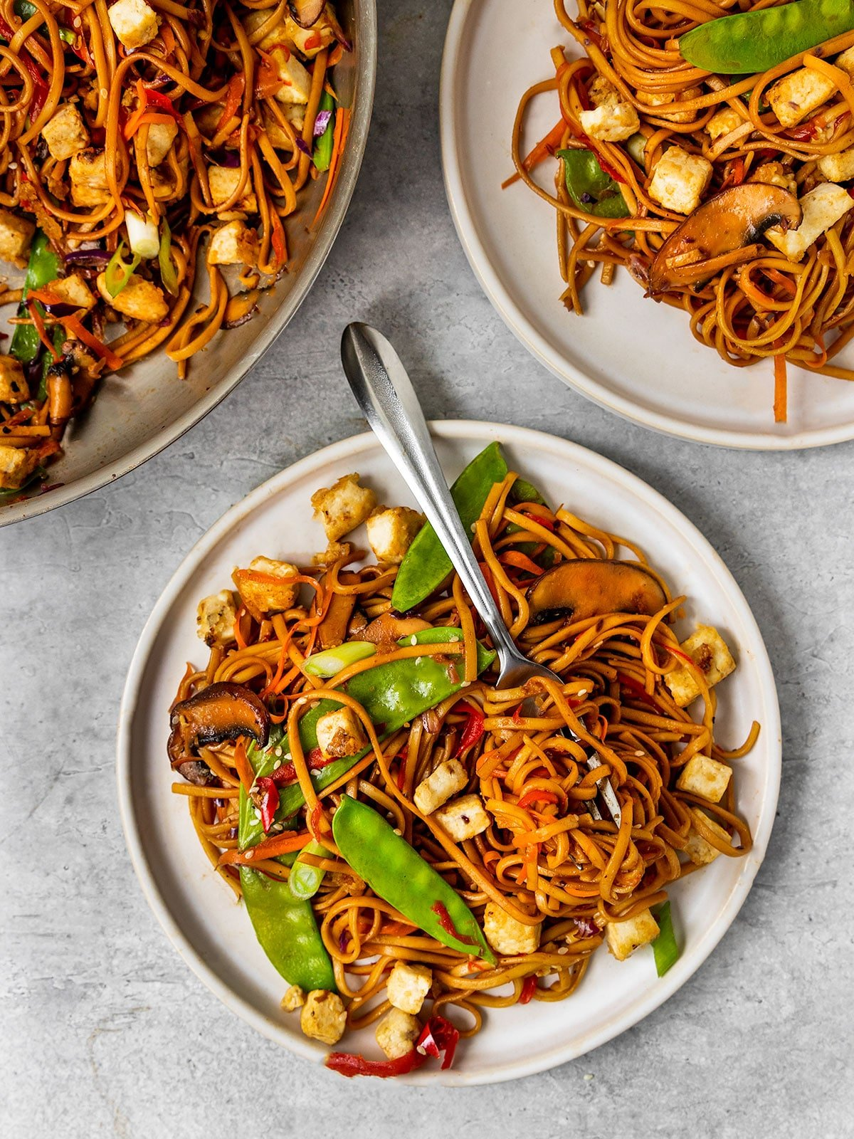 three plates of vegetable lo mein noodles with veggies and tofu