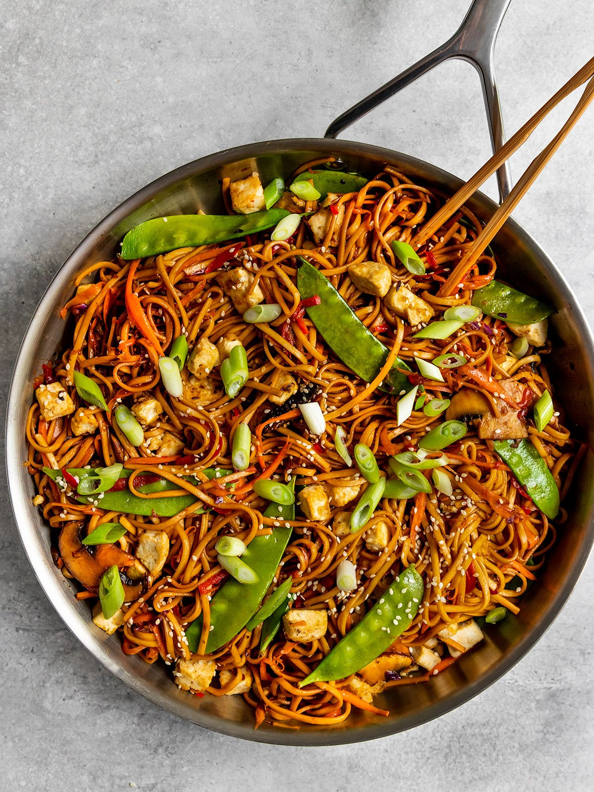 a pan of lo mein noodles with tofu, snap peas, carrots, peppers, cabbage, and green onions