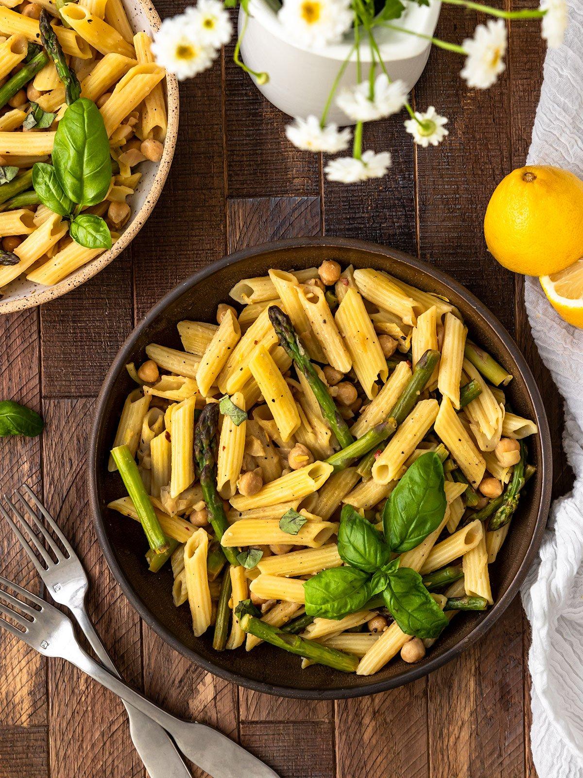 a bowl of penne with lemon sauce, asparagus, and basil