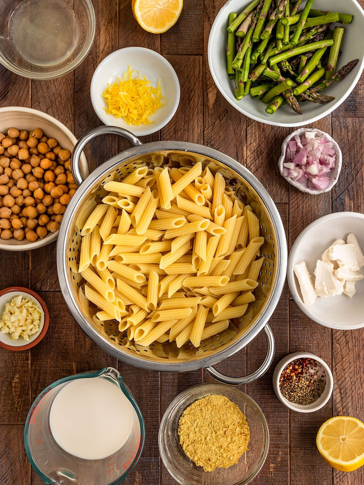 ingredients for penne pasta of chickpeas, garlic, lemon, asparagus, oat milk, nutritional yeast, spices, and butter