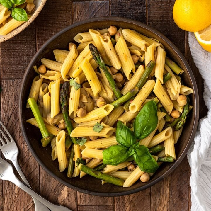 a bowl of penne with lemon sauce, asparagus, and basil