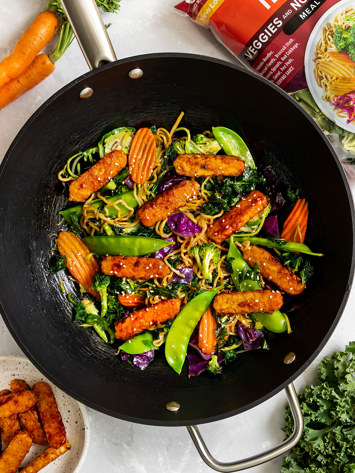 a wok full of asian vegetables, noodles, and tempeh stir fry