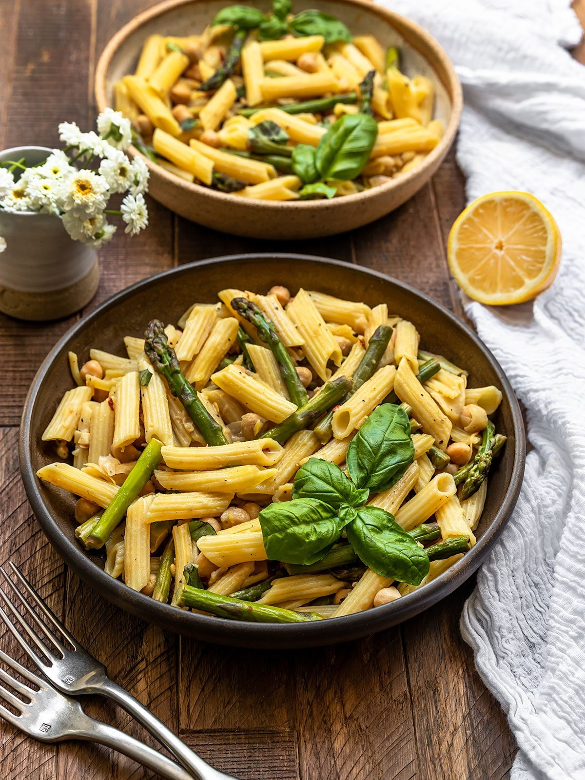 two bowls of penne pasta with asparagus, lemon, and basil