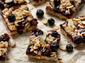 blueberry layer bars with almond crumble and blueberries on top of parchment paper