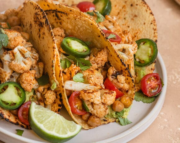 three tacos filled with chickpea, cauliflower, cherry tomatoes, jalapeno slices, cilantro, and a wedge of lime on a plate