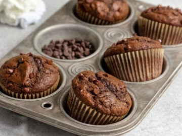 muffin pan filled with chocolate muffind with chocolate chips in cupcake liners