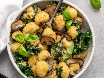 bowl of gnocchi with mushrooms, kale, basil, and cream sauce