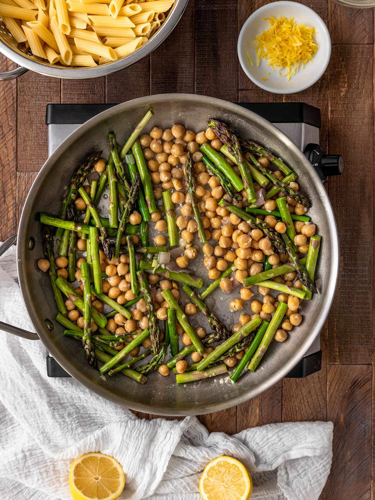 adding asparagus and chickpea to pan to cook