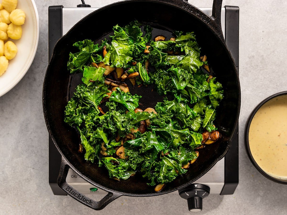adding massaged kale to skillet with crispy mushrooms
