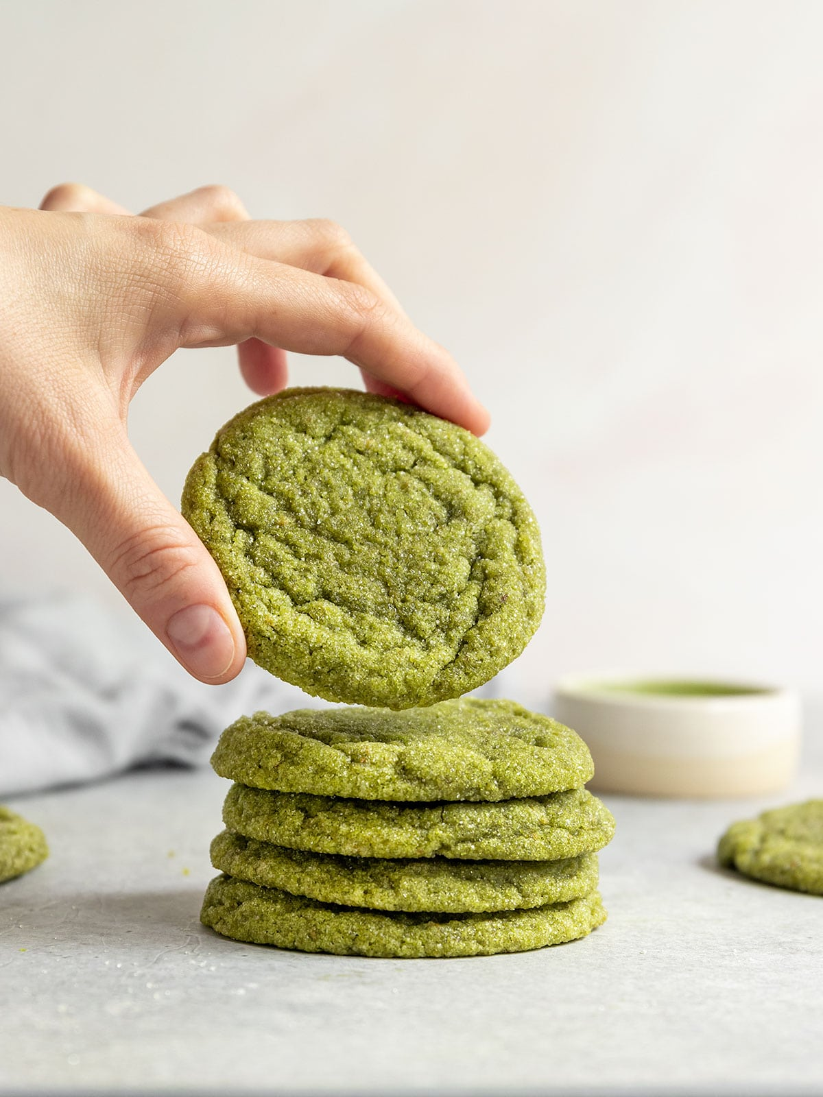 lifting a matcha sugar cookie from a stack of cookies