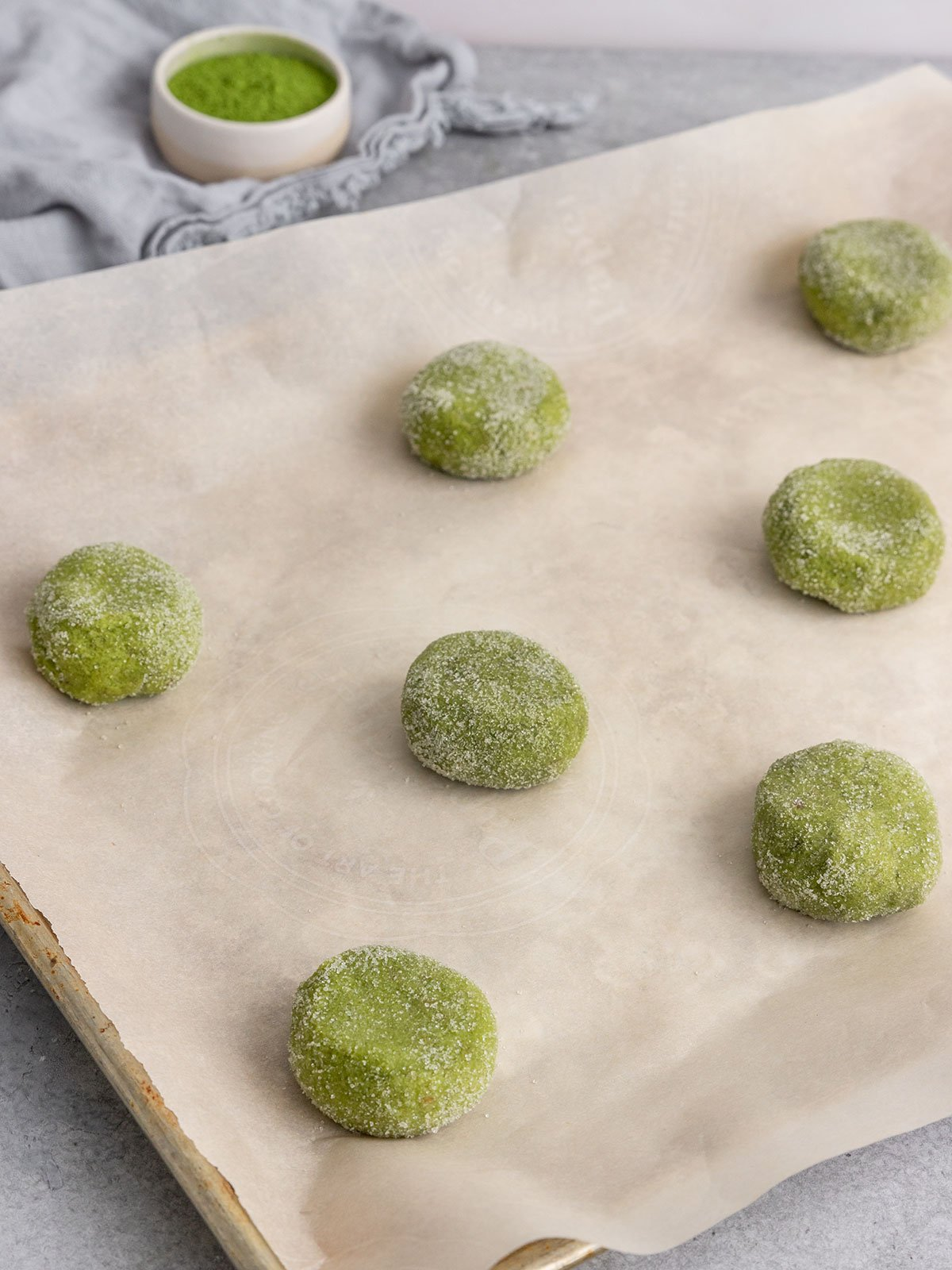 matcha sugar cookie balls on a parchment lined baking tray before baking