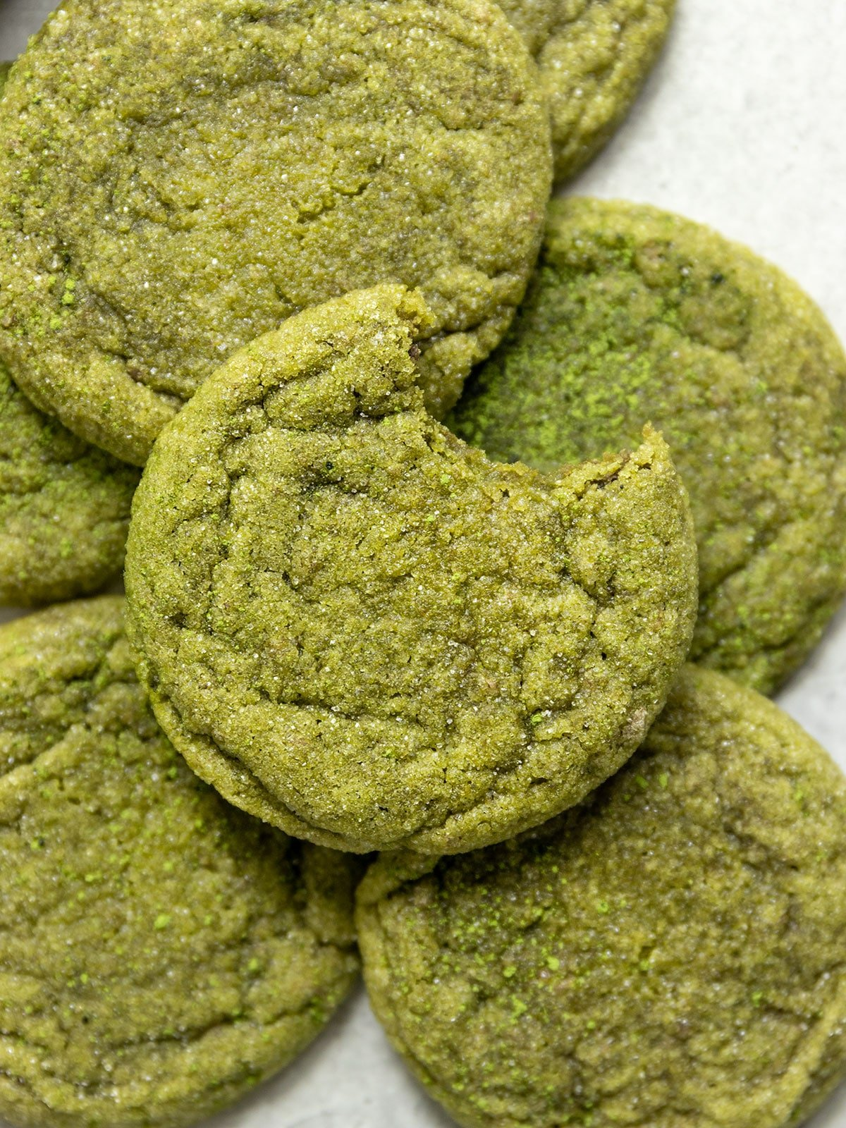 stack of green matcha sugar cookies one with a bite taken out