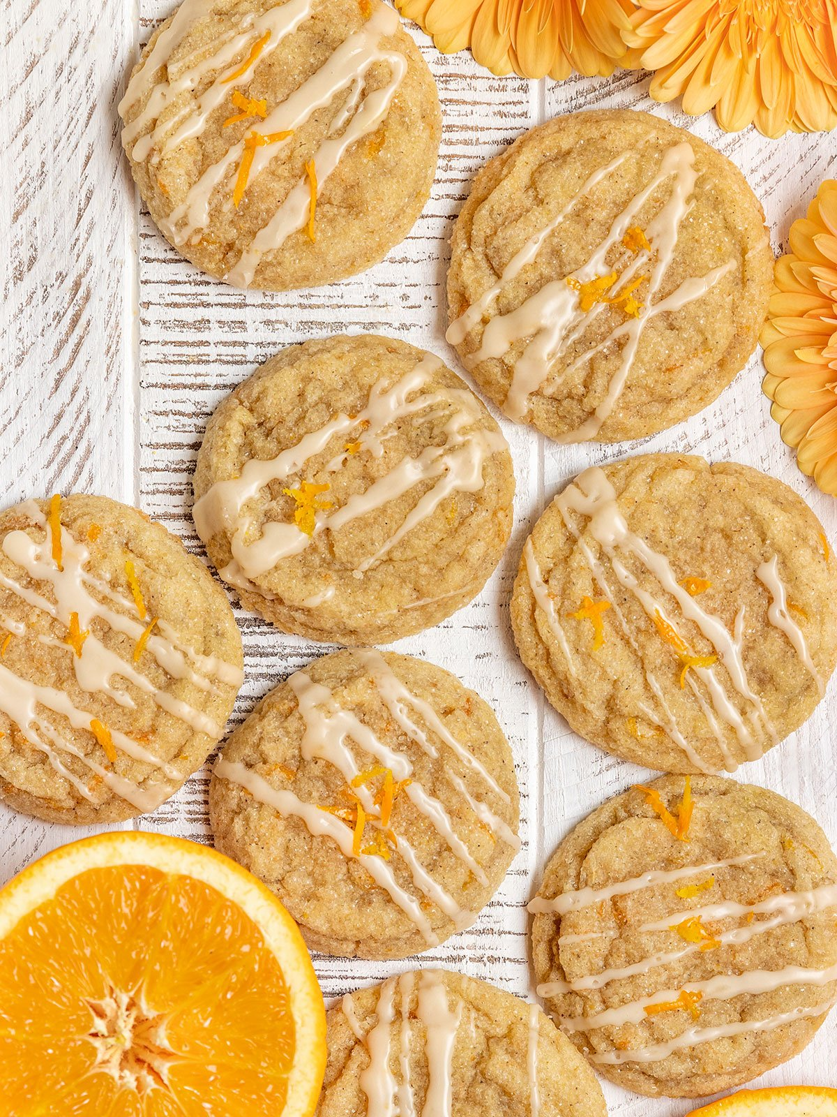 orange cookies with glaze and orange zest layered on a white wood board with fresh orange slices