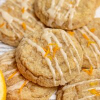 orange cookies with glaze and orange zest layered on a white wood board