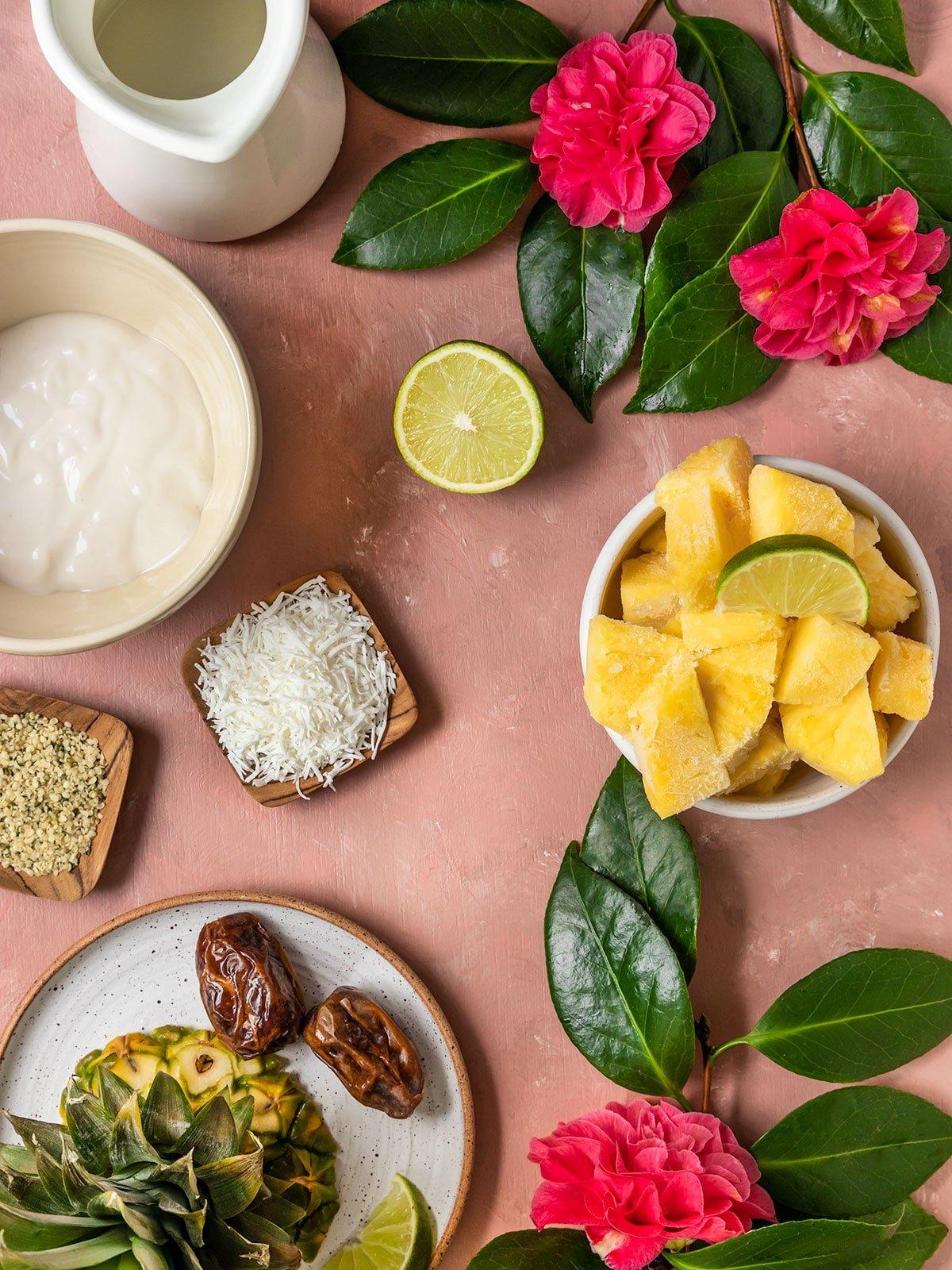 pineapple smoothie ingredients of frozen pineapple, dates, lime, coconut, yogurt, oat milk, hemp seeds