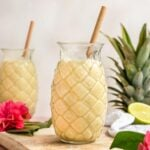 two pina colada smoothies in pineapple shaped glass