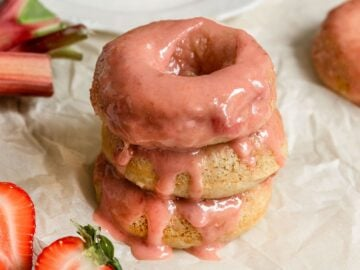 stack of three donuts with strawberry rhubarb glaze dripping off top