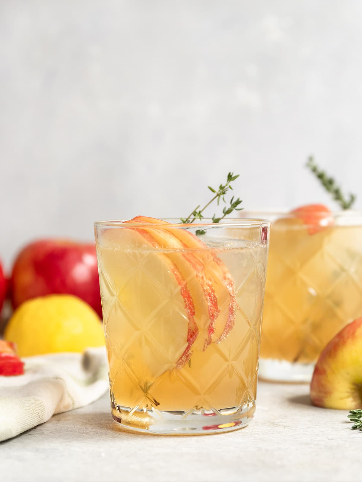 apple bourbon cocktail with apple slices and dried thyme