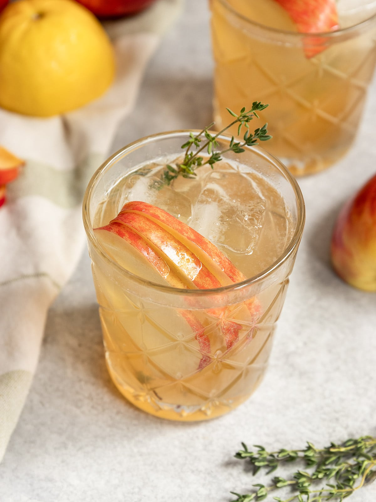 two bourbon cocktails with apple slices and thyme