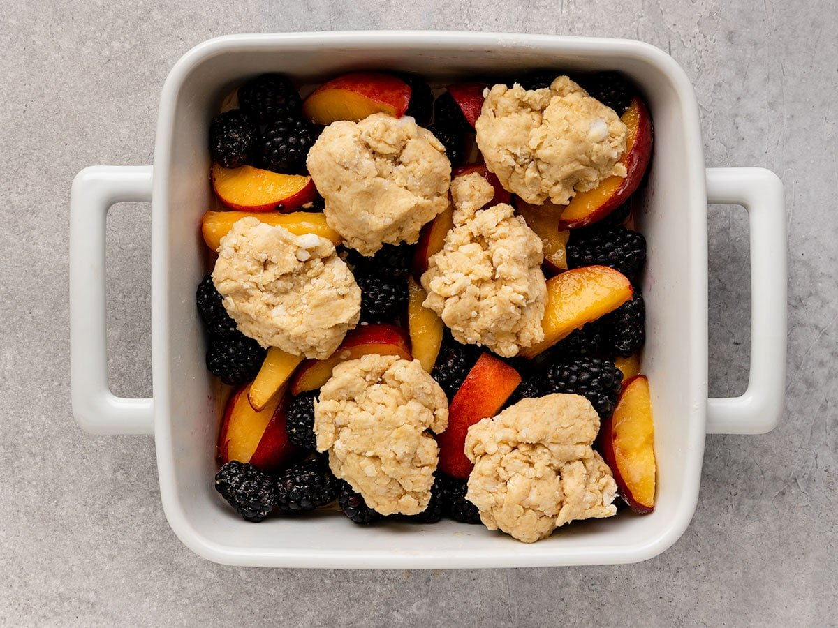baking tray filled with blackberries and peach slices topped with a cobbler dough before baking