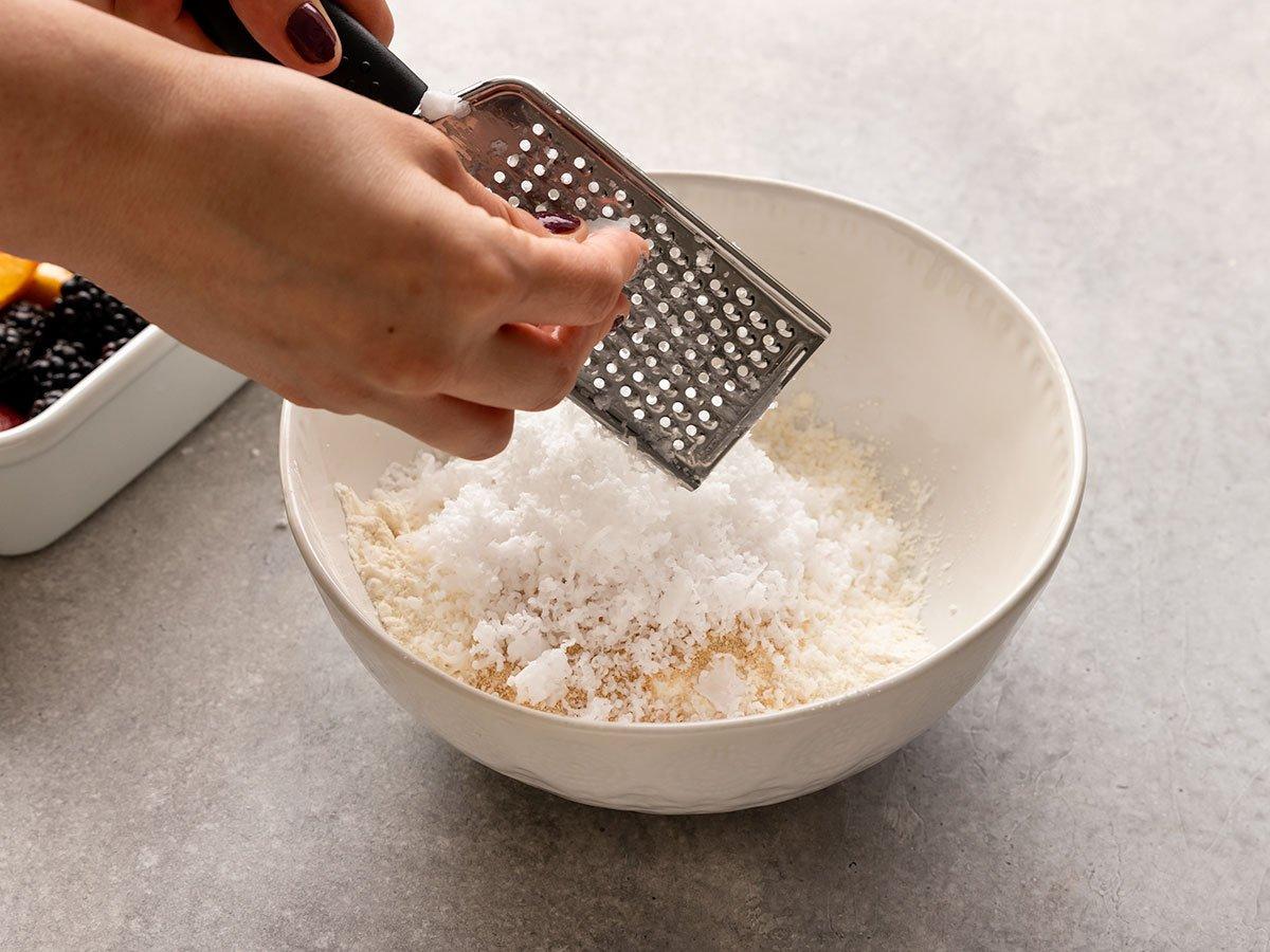 adding frozen coconut oil to bowl
