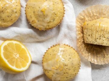 multiple lemon poppyseed muffins with lemon glaze and fresh lemons