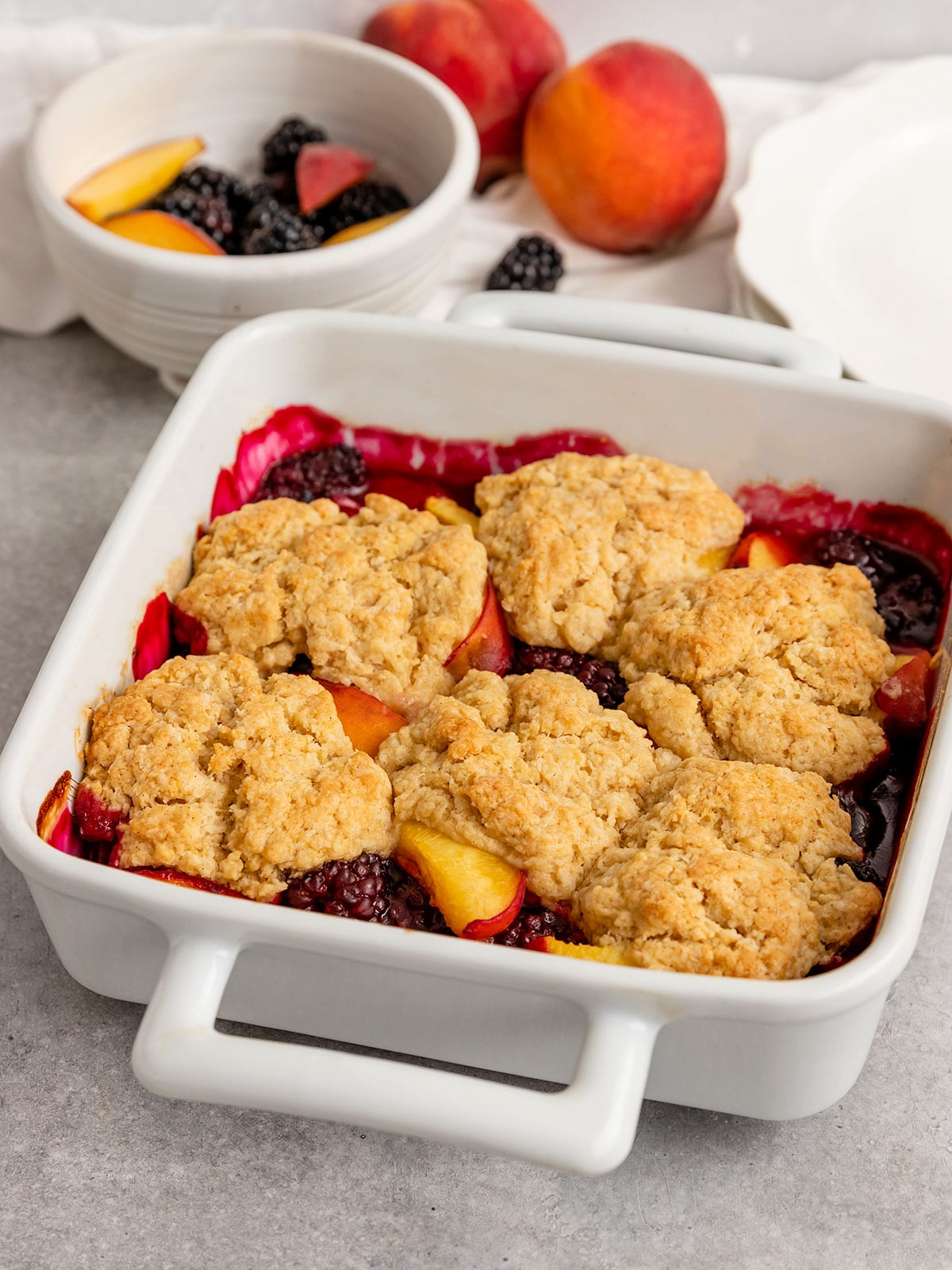 an 8*8 baking pan full of cooked blackerries and and peaches with a cobbler dough on top