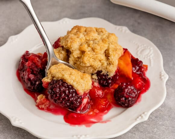 a plate of blackberry peach cobbler getting a spoonful taken out
