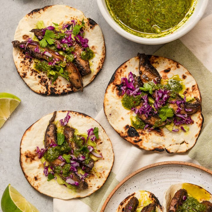 flour tortillas filled with mushrooms, chimichurri sauce, purple cabbage, with extra limes and a bowl of chimichurri sauce on the side