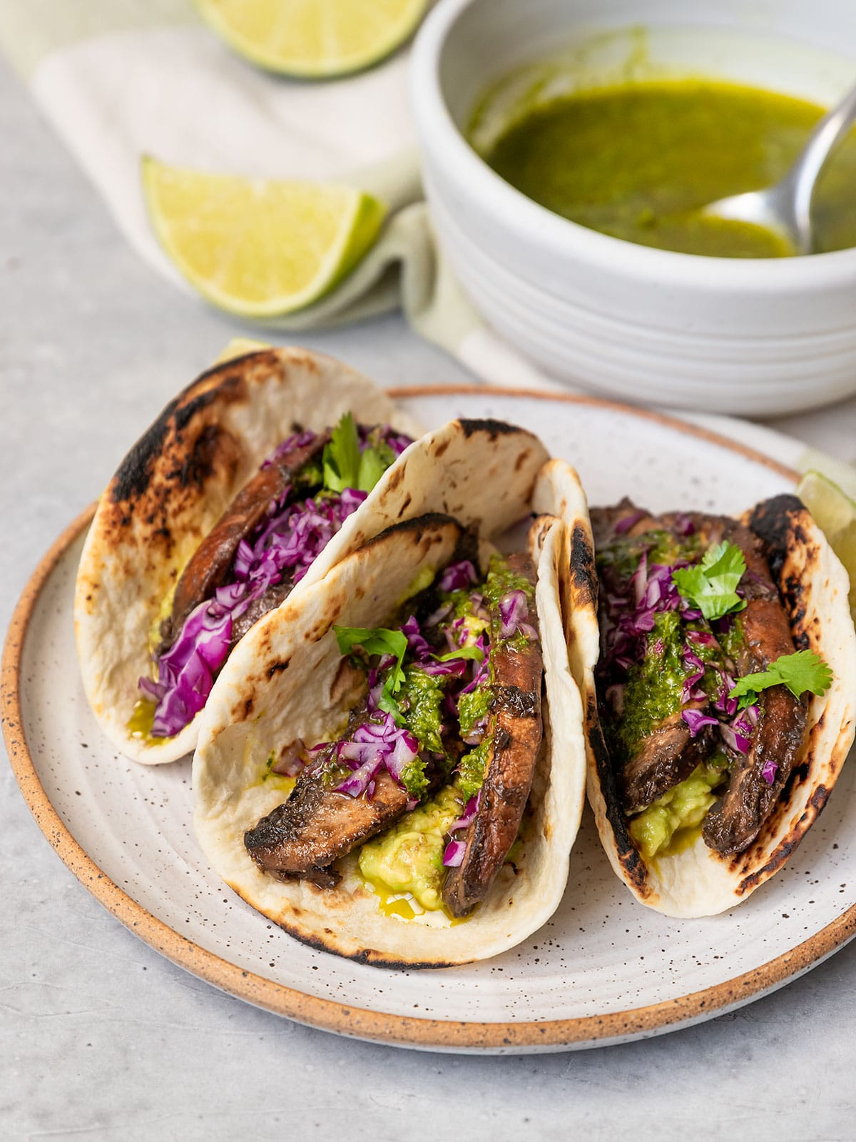 three tacos filled with portobello mushroom slices, avocado, chimichurri sauce, purple cabbage, and cilantro