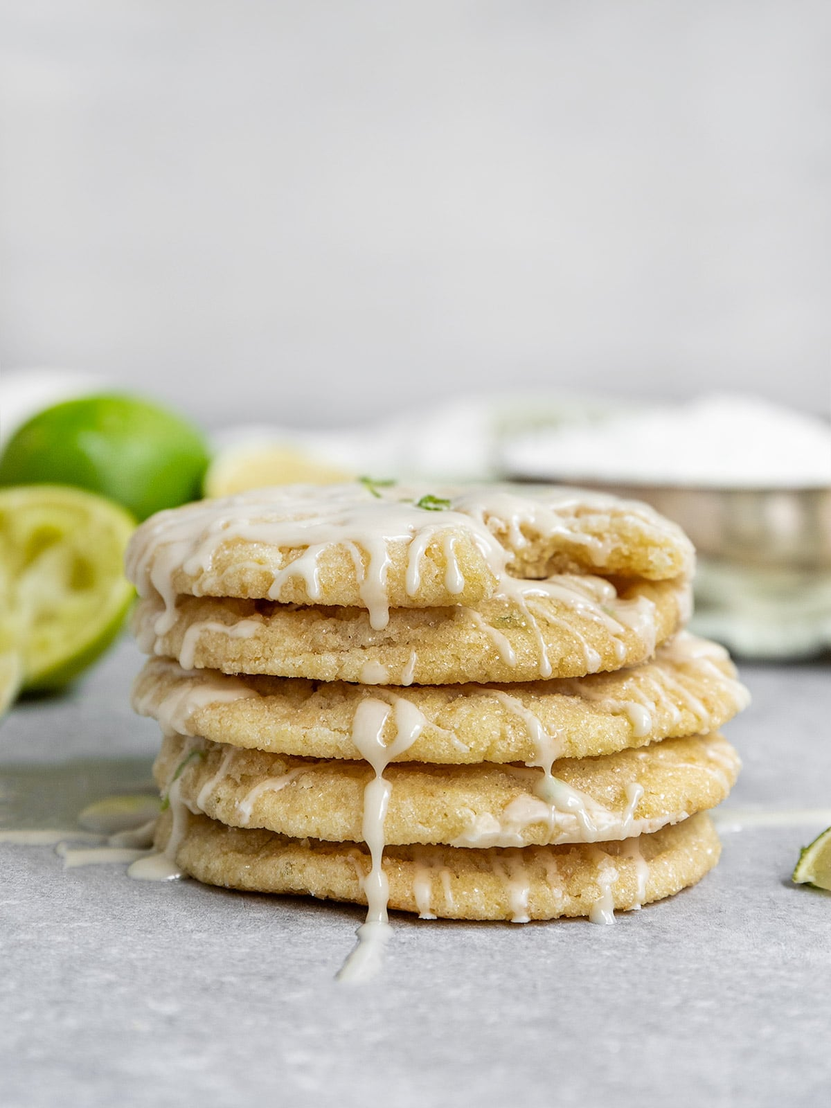 stack of 5 coconut lime sugar cookies with glaze dripping off sides